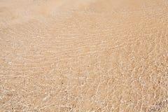 Textur av sand under grunt krusningsvatten Arkivbild