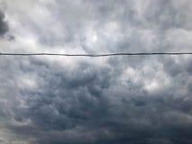 Textur av svart spände hög-spänning trådar för elektricitet mot en bakgrund av mörker - blå vresig stormig himmel med regnmoln fotografering för bildbyråer