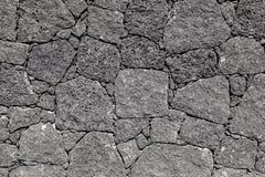 Textur av svart vulkaniskt vaggar väggen från Lanzarote, kanariefågel I royaltyfria foton