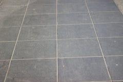 Textur av tegelplattor för grå färgfyrkantstenläggning på den hela ramen Arkivbilder