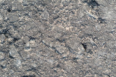 Textur av vägasfalt med många sprickor, sprickor, bucklor och gropnärbild royaltyfri bild