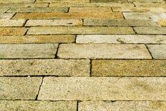 Textur av yttersida av den gammal sten stenlade vägen, trottoartexturbakgrund Royaltyfri Foto
