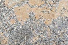 Textur av yttersidan av en gammal antik vägg med ett murbruklager som förstörs från fuktighet, många sprickor, blåsor på väggen Arkivbild