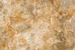 Textur av yttersidan av en gammal antik vägg med ett murbruklager som förstörs från fuktighet, många sprickor, blåsor på väggen Royaltyfria Bilder