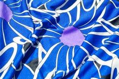 Textur bakgrund, modell Kvinnors blåa siden- klänning På en abs Arkivbild