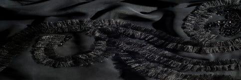 Textur bakgrund, modell svart tygsilk Med sydd patte Fotografering för Bildbyråer
