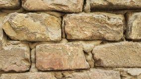 Textur för bakgrund för tapet för stentegelstenvägg Stäng sig av gammal guling vaggar upp tegelstenar med cementmodellen royaltyfri foto