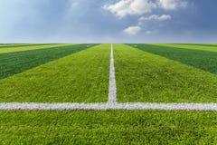 Textur för grönt gräs i fotbollfält med himmel. fotografering för bildbyråer