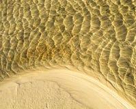 Textur för havsbotten, gula sandvågor i grunt vatten. Arkivbilder