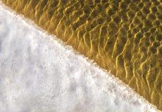 Textur för havsbotten, gula sandvågor i grunt vatten. Royaltyfri Foto