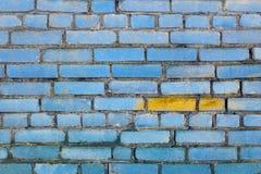 Textur för tegelstenväggen målade blått med den gula fläcken Royaltyfri Foto