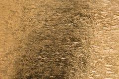 Textur för yttersida för ark för guling för guld- folie skinande metallisk som bakgrund Arkivfoto