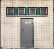 Textur med den lilla fyrkantiga fönster och metalldörren Arkivfoto