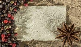 Textur med ett ställe som skriver ett recept, ett skrynkligt papper och kryddor Fotografering för Bildbyråer
