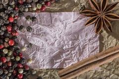 Textur med ett ställe som skriver ett recept, ett skrynkligt papper och kryddor Royaltyfria Foton