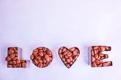 Textur med ordförälskelsen för valentin daginskriften som göras från utvald brun aromatisk bakgrund för Arabicakaffebönor arkivfoton