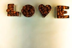 Textur med ordförälskelsen för valentin daginskriften som göras från utvald brun aromatisk bakgrund för Arabicakaffebönor royaltyfri foto