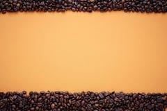 Textur ram för kaffeböna på orange bakgrund, utrymme för text arkivbilder
