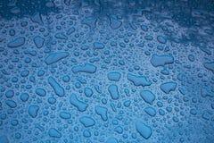 Textur - vattendroppar på en blå kropp av bilen Royaltyfri Bild