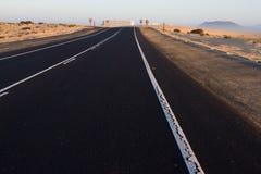 Textura áspera del camino Manera negra del asfalto con la línea blanca en el centro Salida del sol, España, Fuerteventura Imagenes de archivo