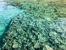 A textura é água salgada iridescente clara azul molhada transparente do mar, mar, oceano com ondas, ondinhas com a parte inferior fotografia de stock