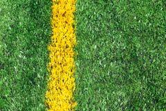 Textura artificial verde do campo de futebol do relvado com linha amarela imagens de stock royalty free