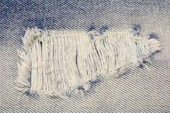 Textura azul de la mezclilla con un agujero y mostrar de los hilos imagenes de archivo