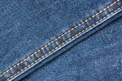 Textura azul de los vaqueros del dril de algodón con las costuras Imagenes de archivo