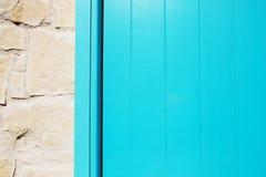 Textura azul de madera de la puerta del tablón cerca de la pared de piedra Fotografía de archivo libre de regalías