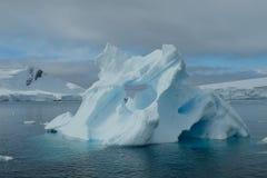 Textura azul original da arte do iceberg da Antártica abaixo do céu nebuloso MONTANHAS NEVADO imagens de stock