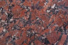 Textura castanho-avermelhado do granito com os pontos pretos e cinzentos Fim acima usado como um fundo imagens de stock