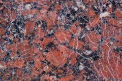 Textura castanho-avermelhado do granito com os pontos pretos e cinzentos Fim acima usado como um fundo fotografia de stock royalty free