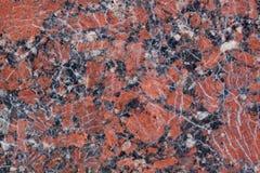 Textura castanho-avermelhado do granito com os pontos pretos e cinzentos Fim acima usado como um fundo imagens de stock royalty free