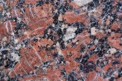 Textura castanho-avermelhado do granito com os pontos pretos e cinzentos usado como um fundo fotos de stock