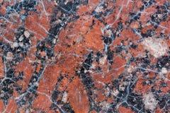 Textura castanho-avermelhado do granito com os pontos pretos e cinzentos usado como um fundo imagem de stock