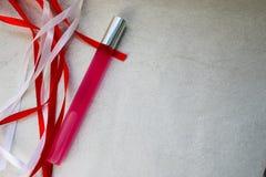 Textura con una botella de perfume cilíndrica larga fina mate rosada, cologne con las cintas festivas hermosas rojas y blancas he foto de archivo