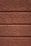 Textura concreta decorativa rojiza de la pared fuera de un edificio imagen de archivo libre de regalías