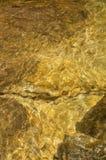Textura da água de rochas douradas imagem de stock royalty free
