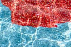 Textura da água no swimmingpool e das reflexões em azul e em vermelho Imagem de Stock Royalty Free