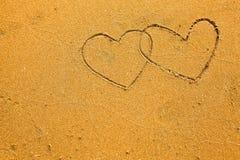 Textura da areia: os corações da inscrição dois Fotografia de Stock