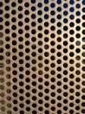 A textura da grelha do metal de Brown/ouro com furos fecha-se Imagens de Stock