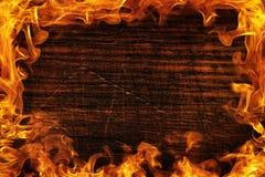 Textura da madeira e do quadro escuros fora do fogo Textura marrom de madeira em torno da chama brilhante ardente Fundo dos painé fotografia de stock royalty free