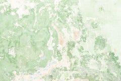 A textura da parede antiga velha é verde, lá é fraturas da camada protetora branca de emplastro dos efeitos foto de stock