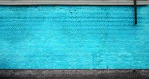 A textura da parede de tijolo de muitas fileiras de tijolos pintados no colo ciano foto de stock royalty free