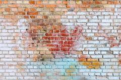 A textura da parede de tijolo velha pintada de cores azuis, vermelhas, amarelas e brancas fotografia de stock