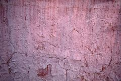 Textura da pintura de descascamento cor-de-rosa velha na parede nas quebras imagens de stock