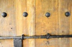 A textura da porta grossa natural de madeira resistente da antiguidade medieval antiga velha com rebites e testes padrões e fecha fotografia de stock