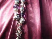 Textura da seda cor-de-rosa com um elemento da corrente do metal e os grânulos do cristal imagem de stock