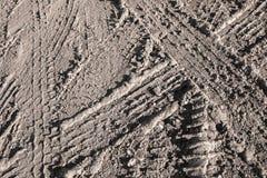 Textura da sujeira da estrada do marrom escuro com trilhas do pneu Fotografia de Stock