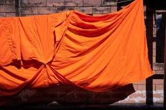 Textura da veste alaranjada de uma monge budista ou de um principiante pendurada no fio imagens de stock